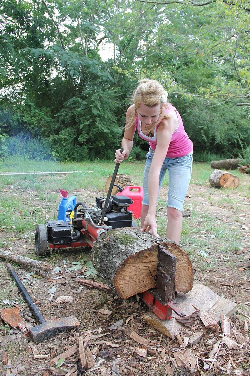 Woman splitting logs and showing gas powered log splitter parts